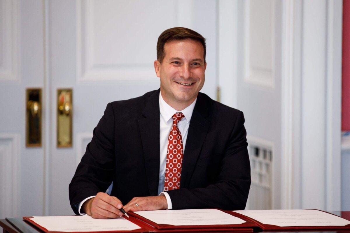 Minister smiling at desk