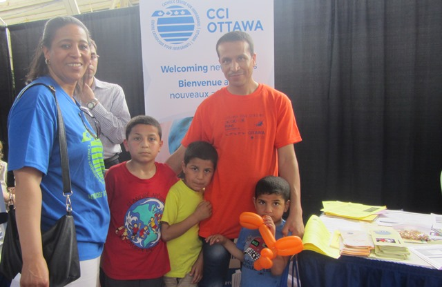 CCI staff Halima Laaroubi with recently arrived refugee Ali Al Ahmed and his children at Welcome Event at Lansdowne Park