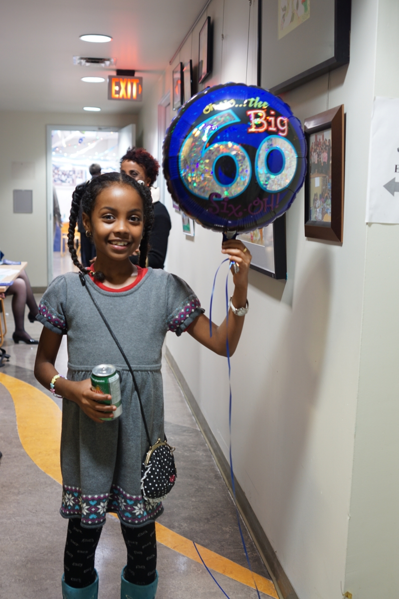 Young woman holds balloon at 60th anniversary celebration