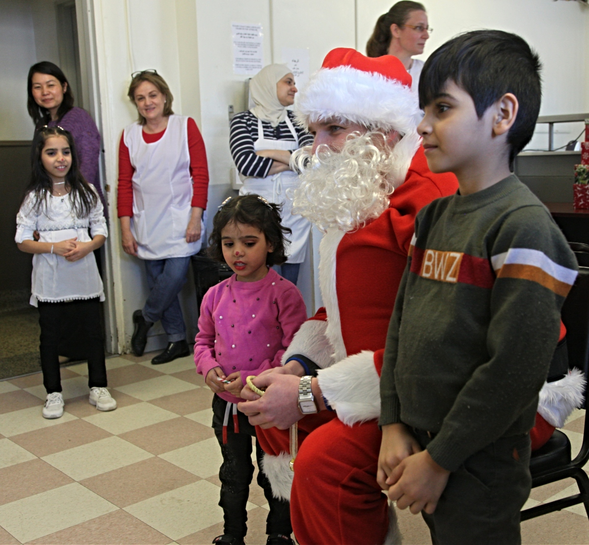 Tw children pose with Santa Claus