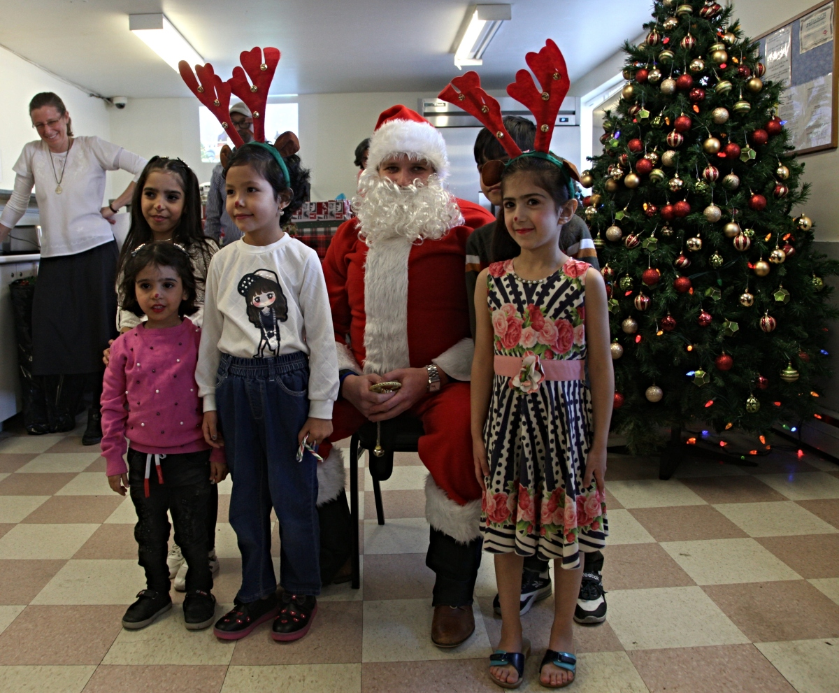Young children pose with Santa Claus