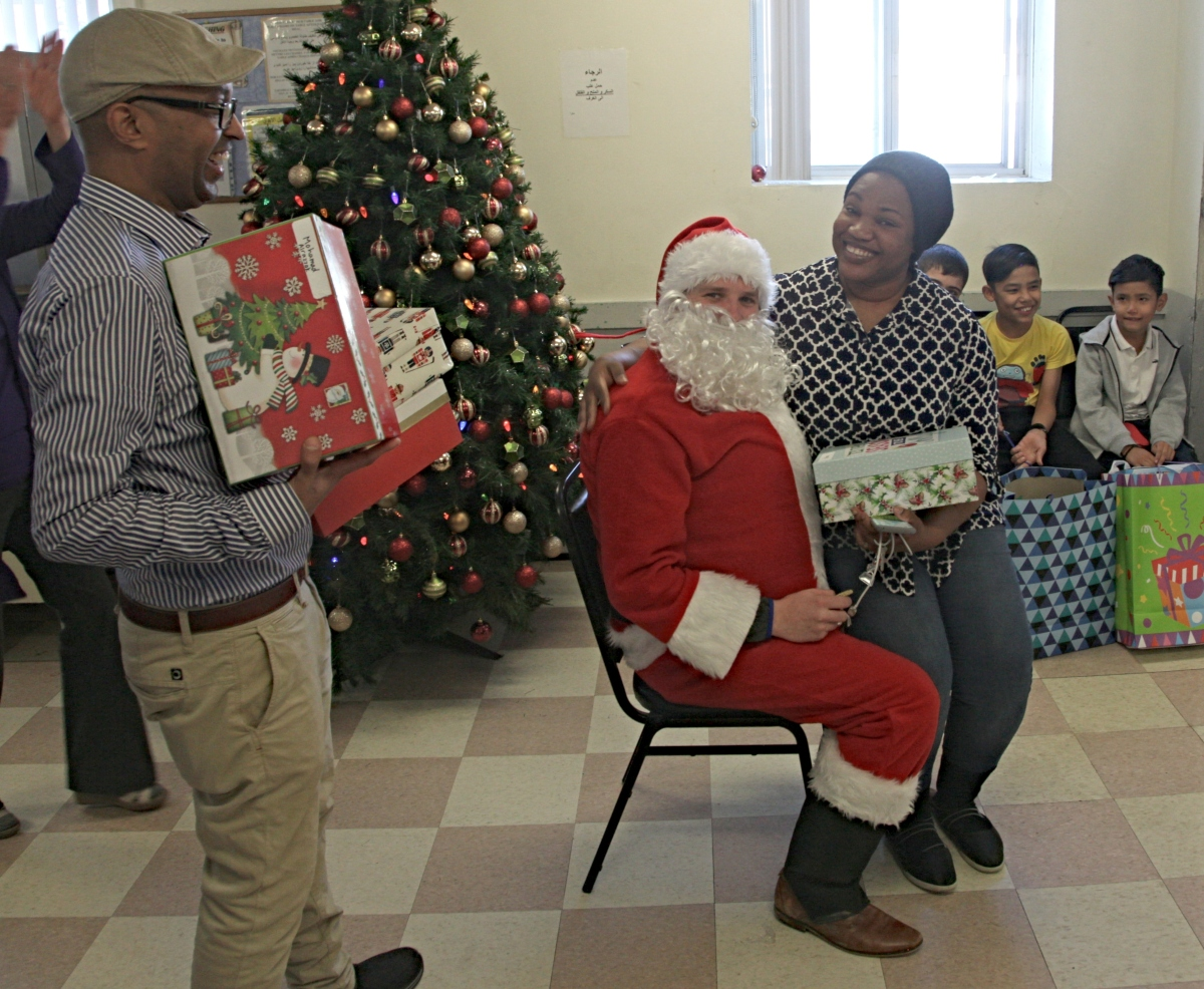 Woman sits om Santa's knee as man hands out gifts