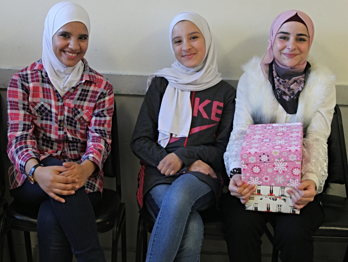 Three young women pose with gifts