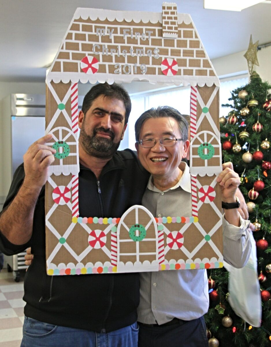 Two men pose with a gingerbread house selfie board