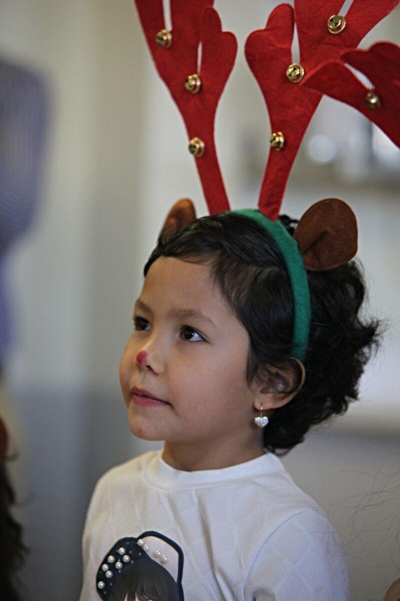 Child wears reindeer hat