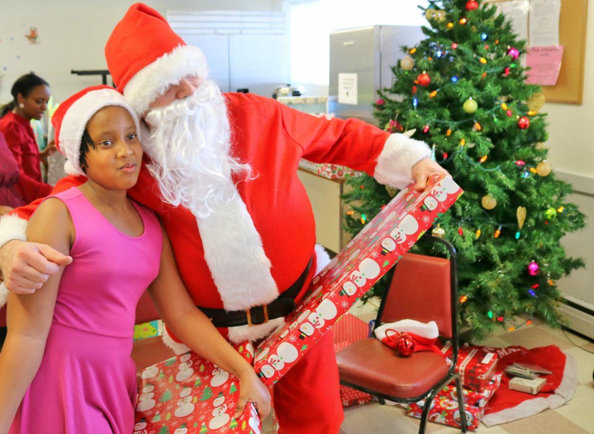 Santa hugs girl with gift