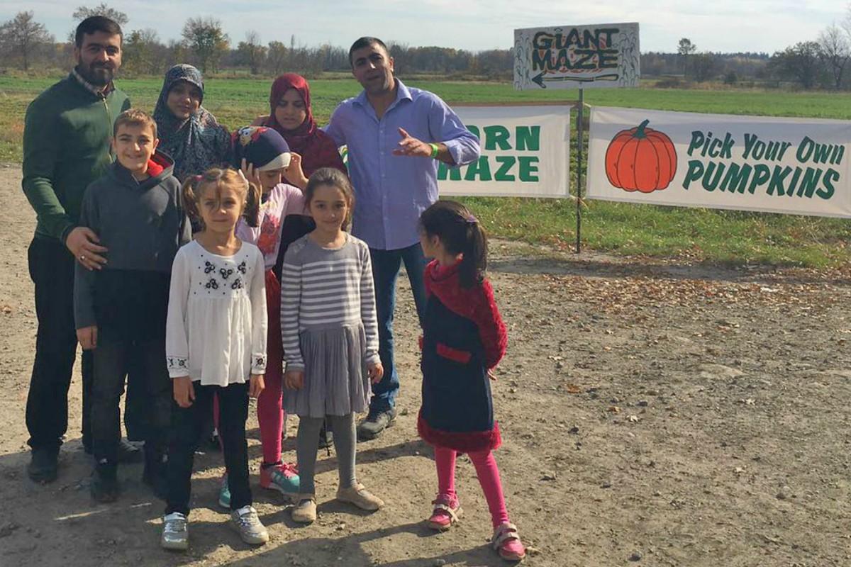 Family poses near farm sign