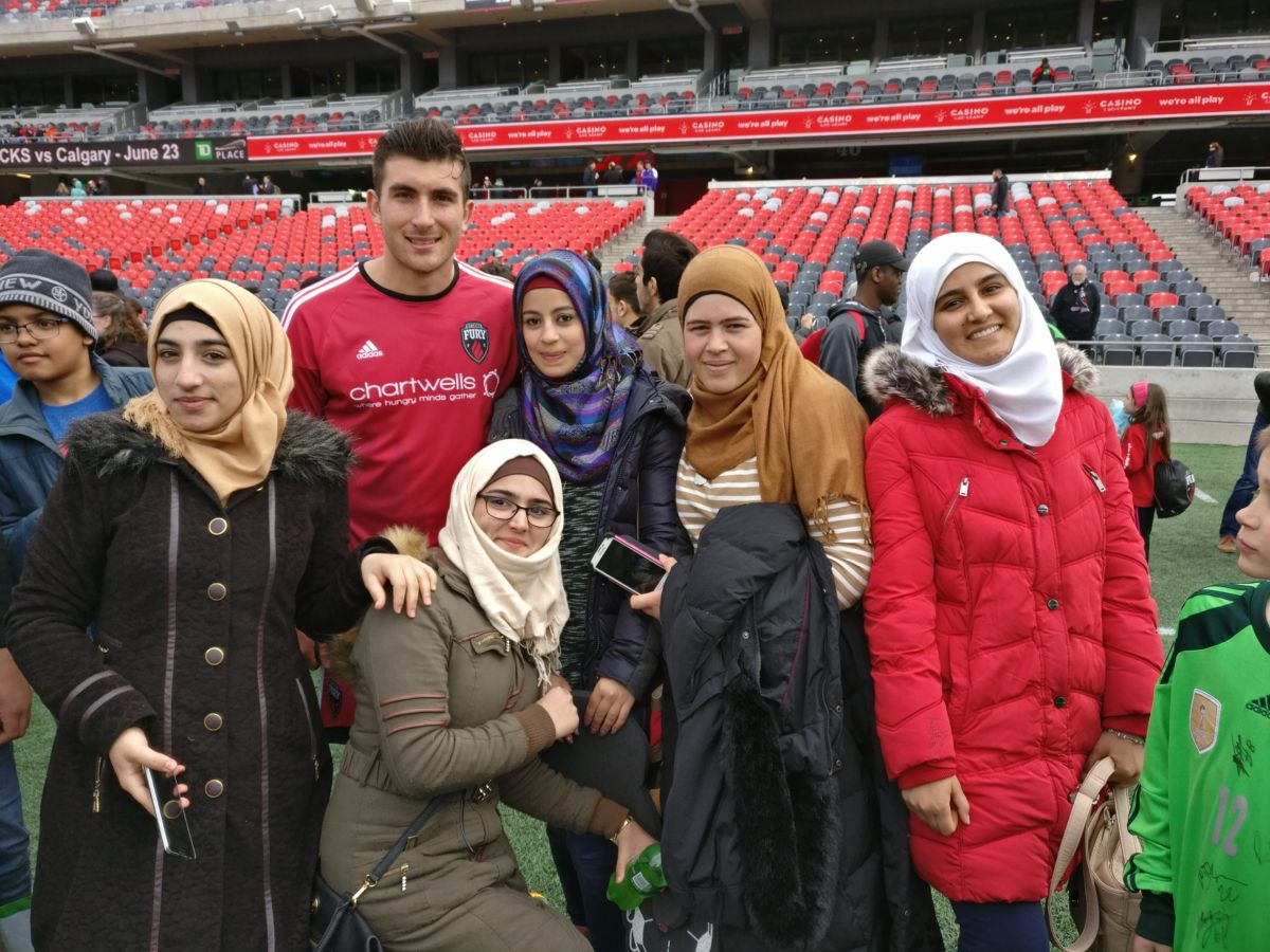 A group of youth newcomers pose with a player from the Ottawa Fury.