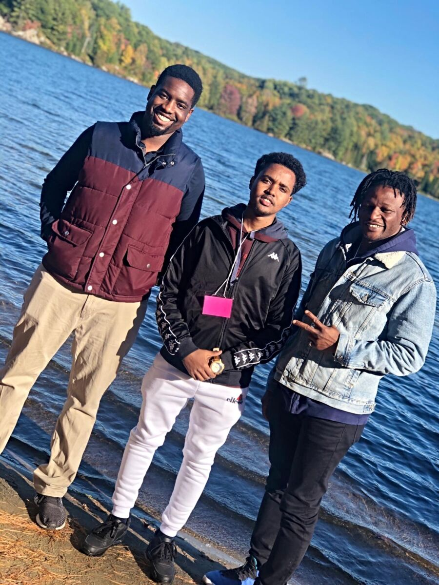 Three young men smiling in front of a lake