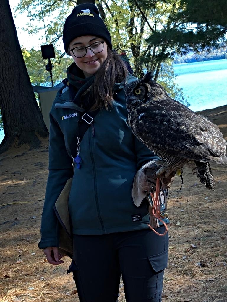 young woman holds an owl on her arm