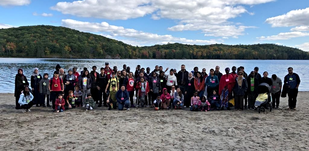 Large group of people standing in front of the lake