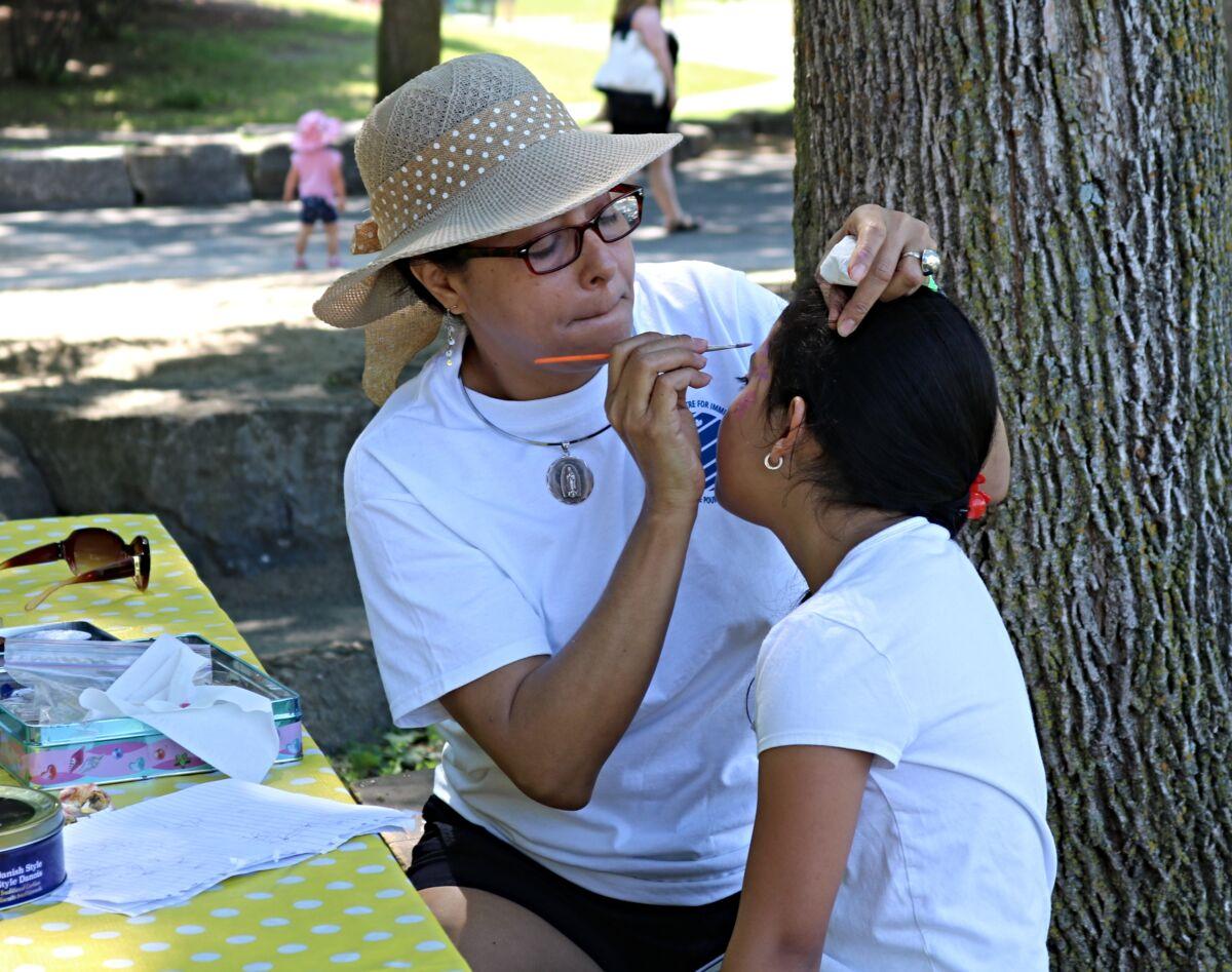 Woman paints child's face.