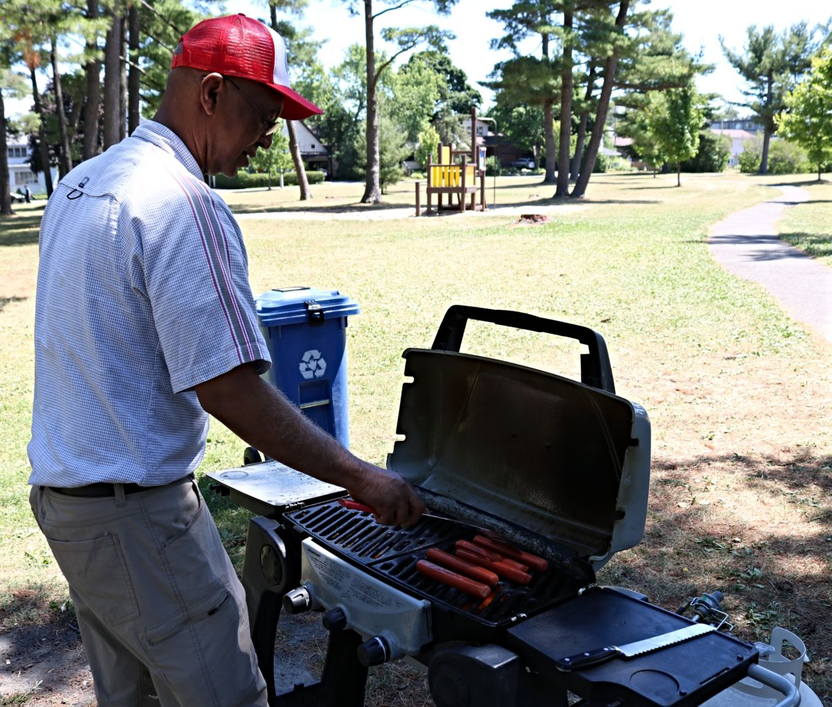 Man cooks hot dogs