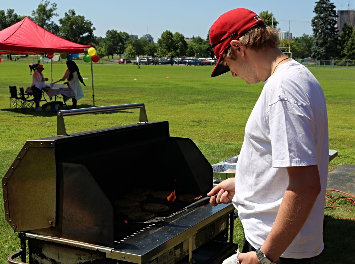Man cooks hamburgers on a barbecue