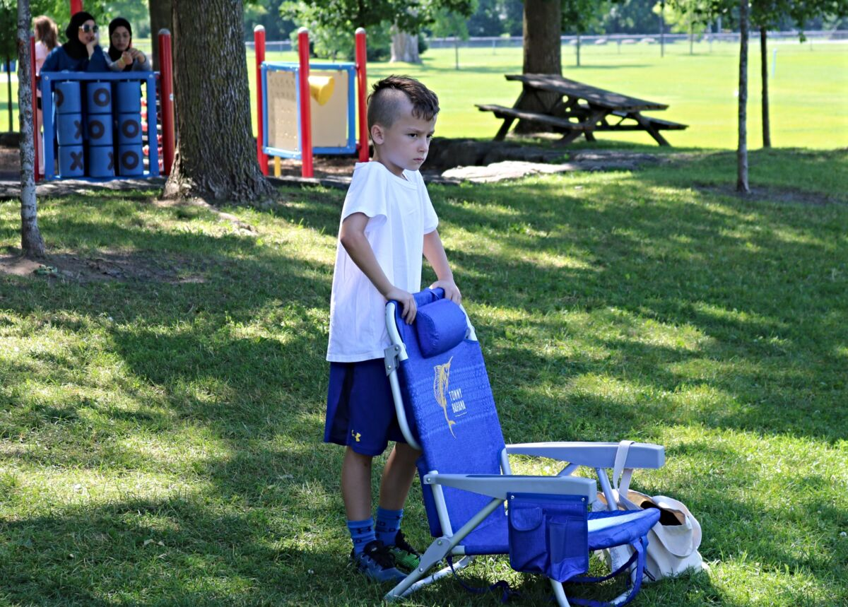 Boy stands at lawn chair