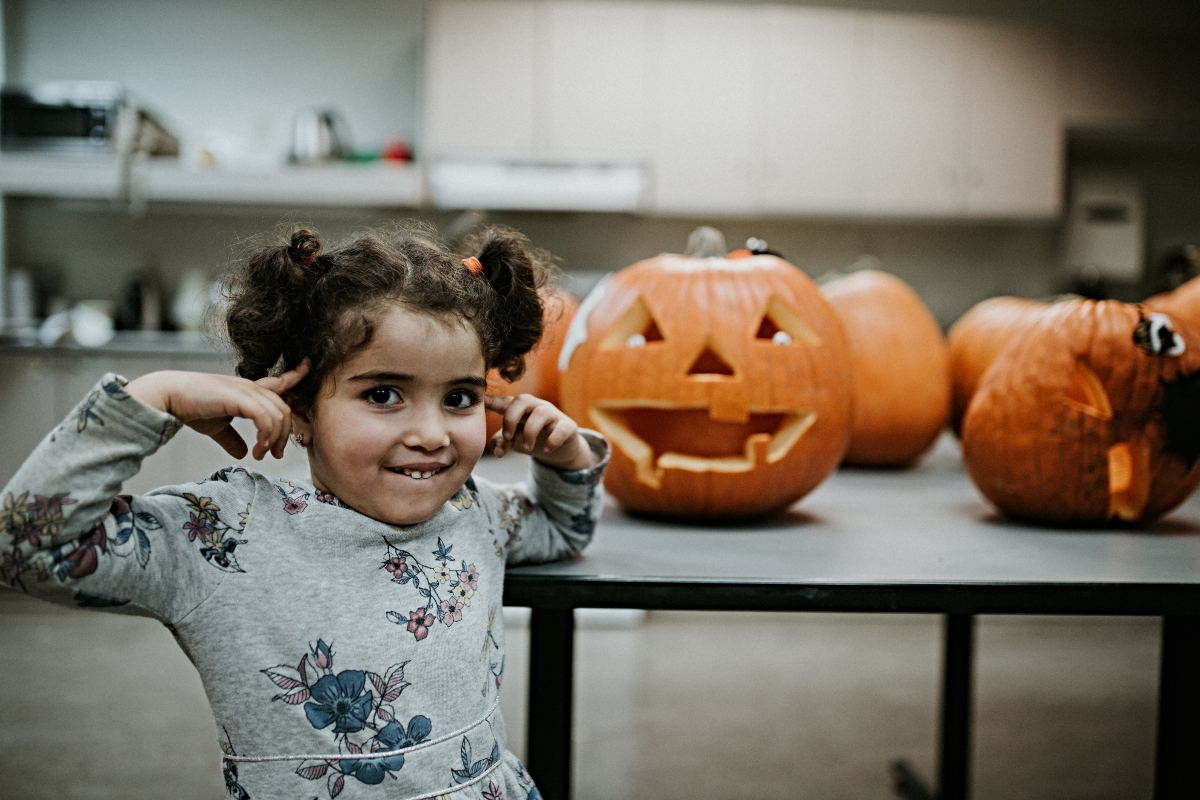 Girl smiles with carved pumpkin