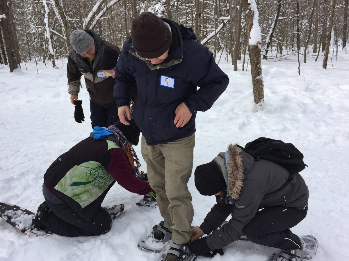 A man puts on snowshoes