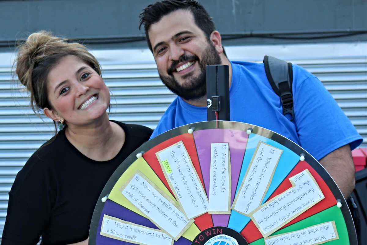 Man and woman smiling in front of roulette wheel