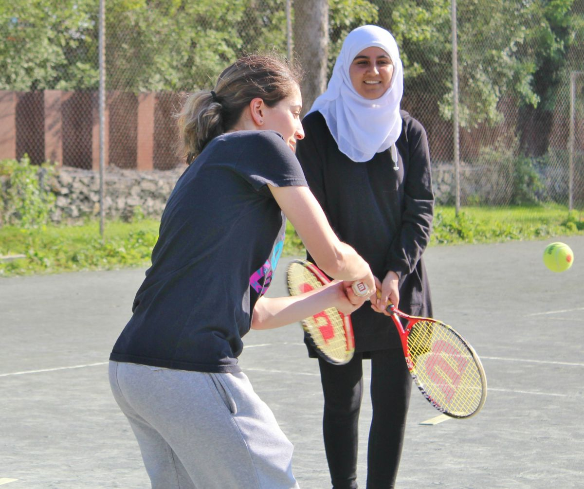 A young newcomer attempts to hit a tennis ball