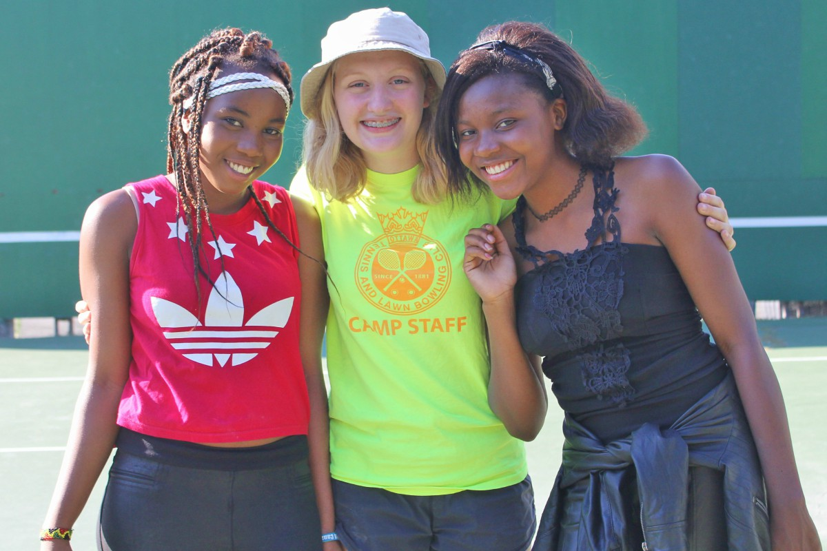 Three young women pose for a photo at the tennis club