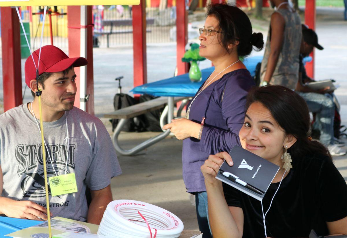 Three people staff the volunteer desk