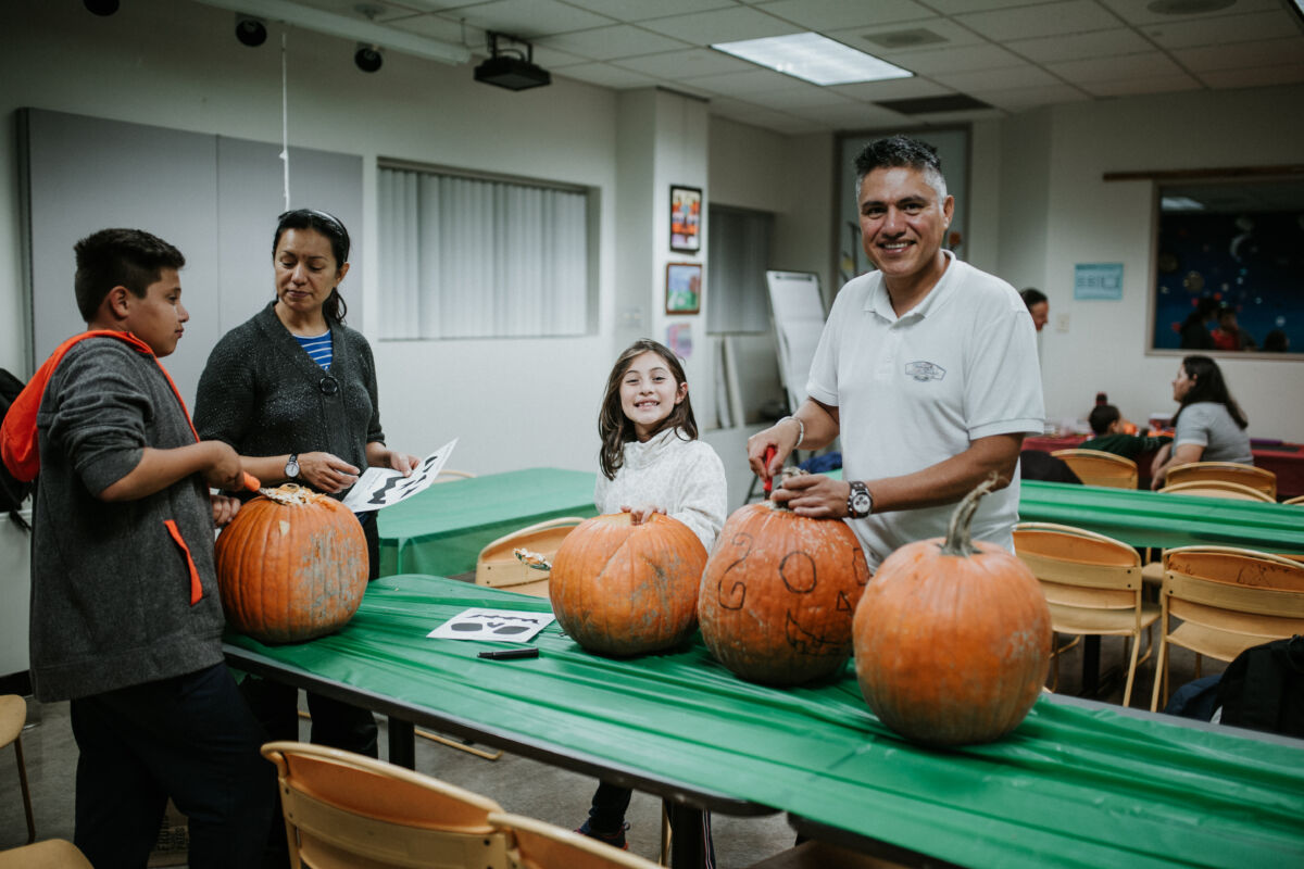 Man and daughter carve pumpkin