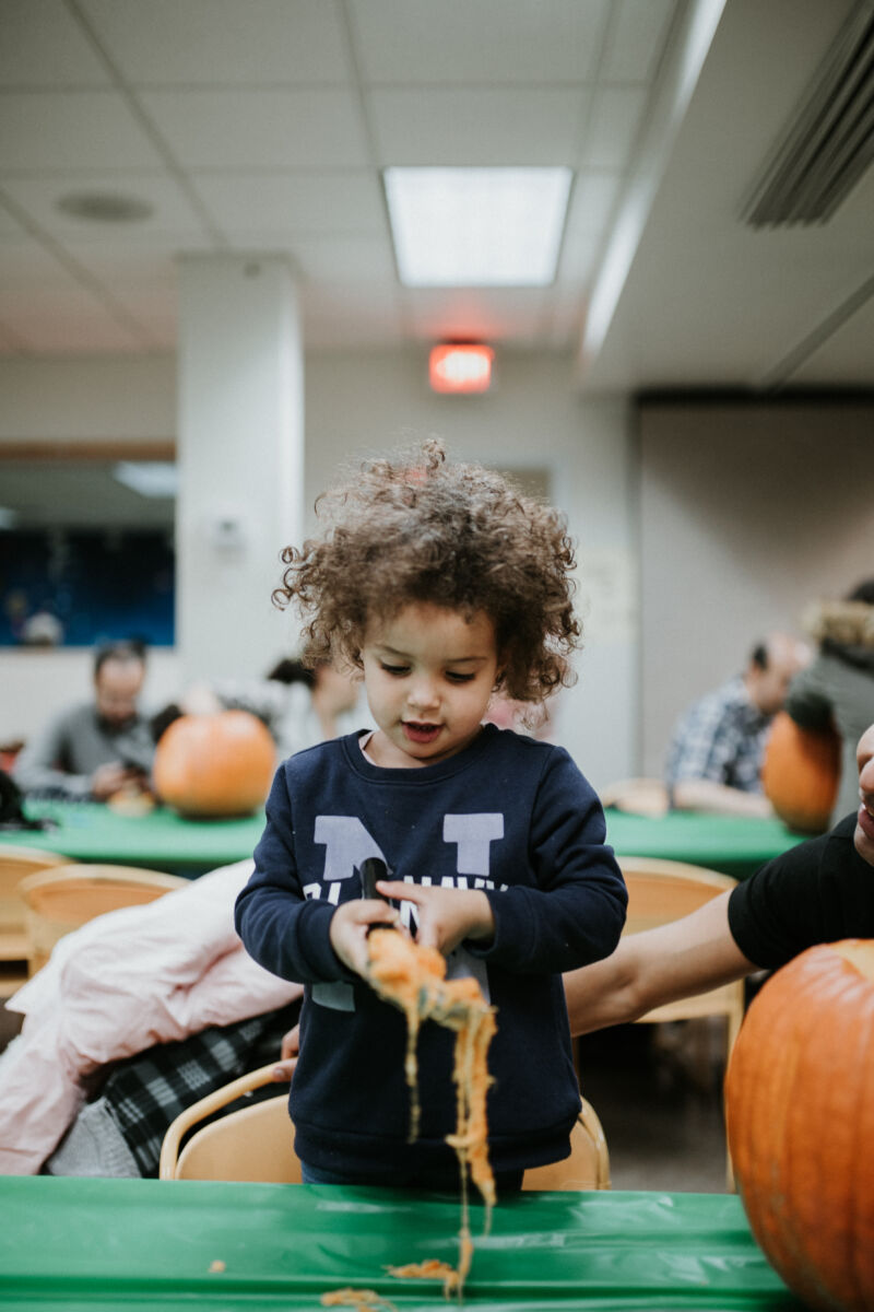 Young girl plays with pumpkin paste