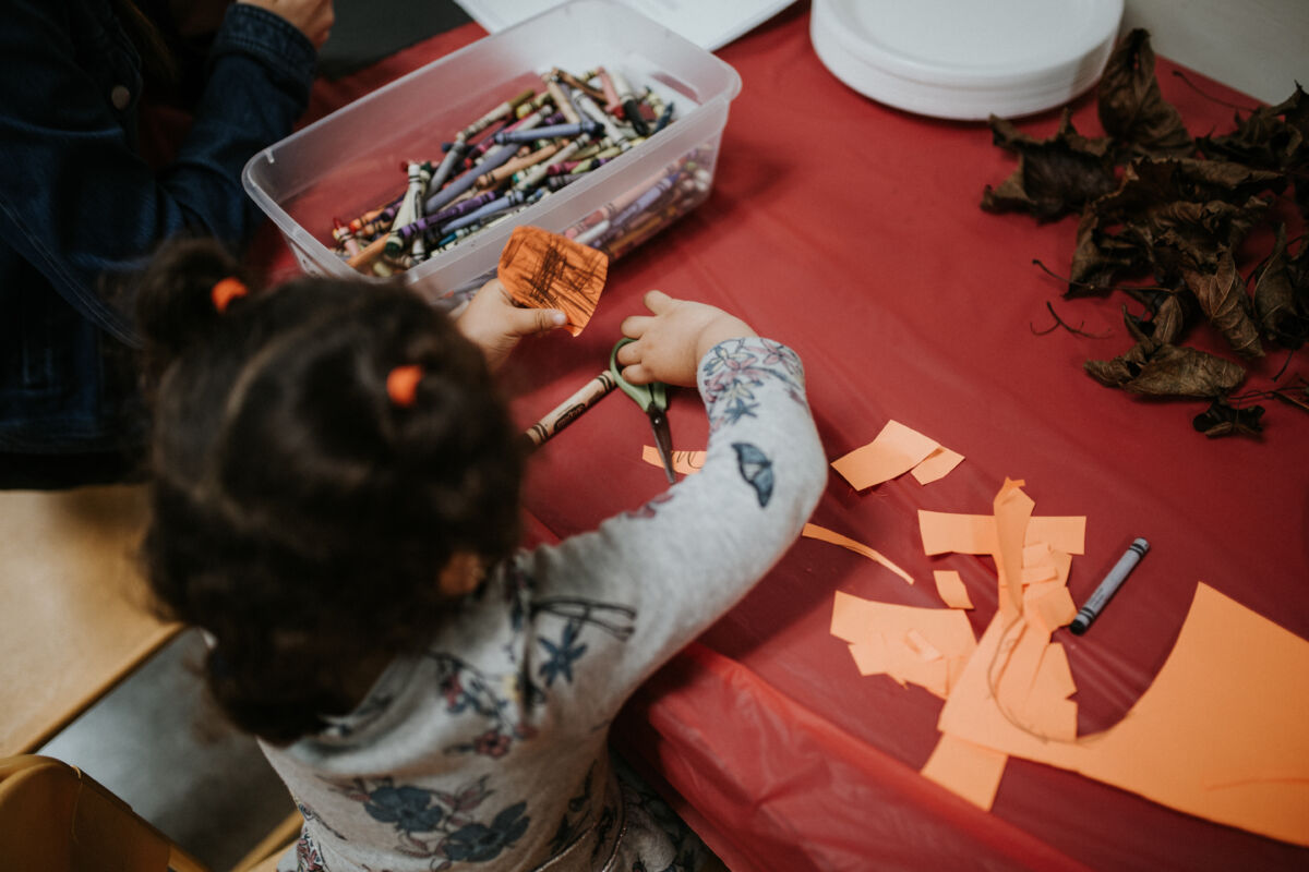 Younh girl uses scissors to create a Halloween decoration
