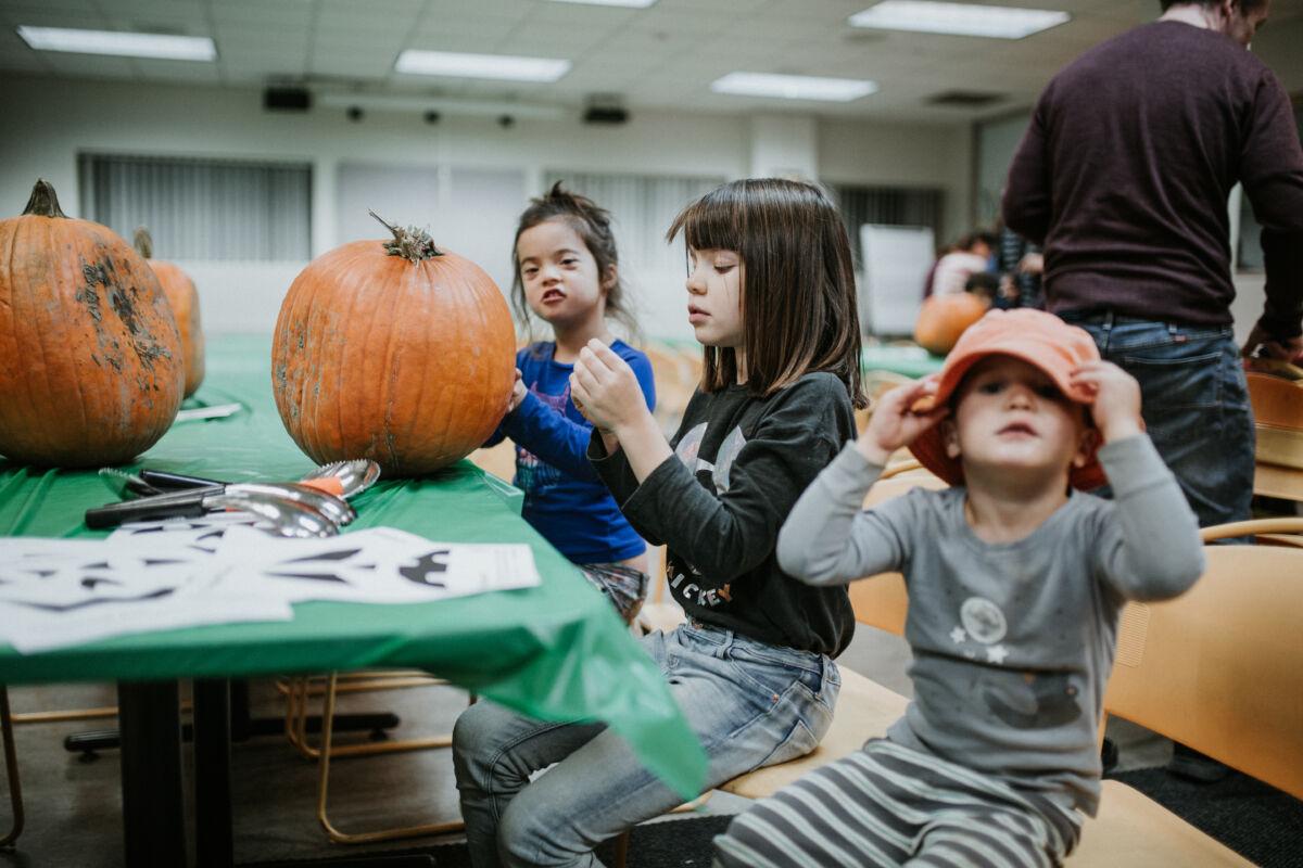 Children play with a pumpkin