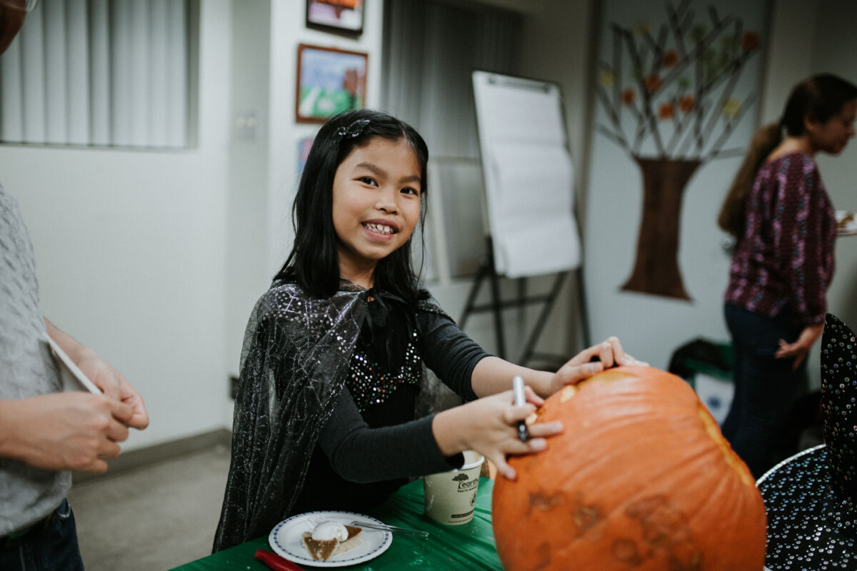 Young girls gets ready to write on her pumpkin