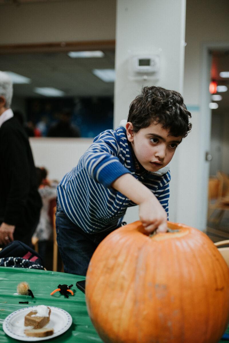 Young boy reaches into a pumpkin