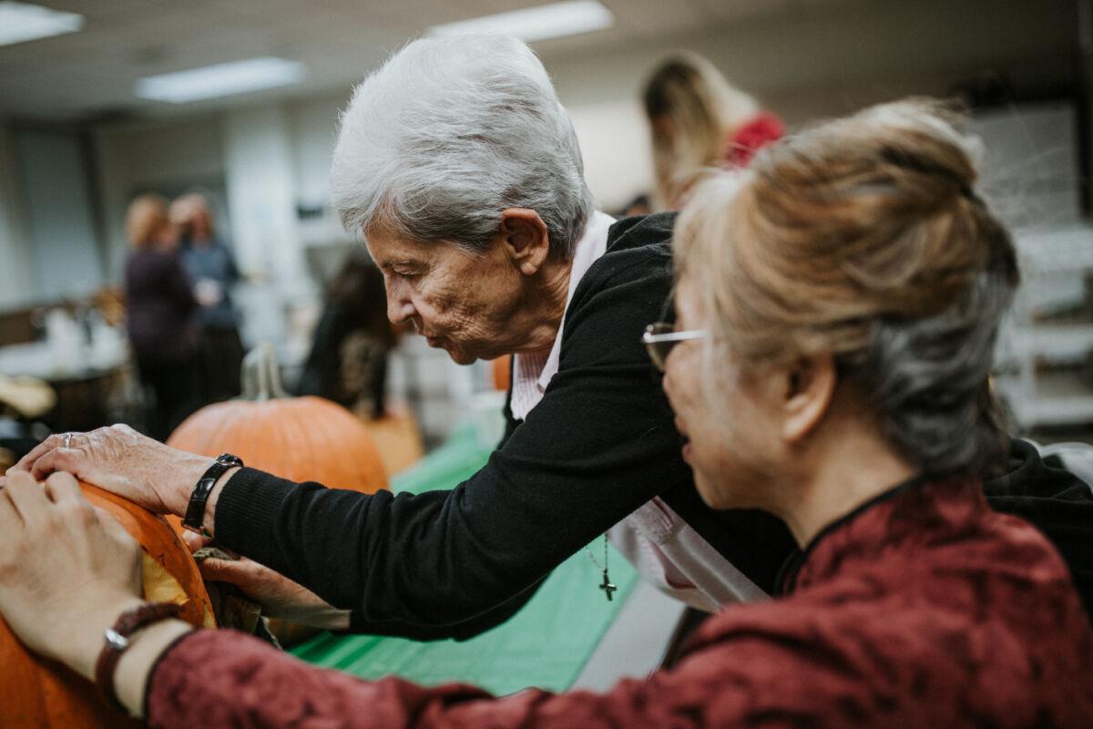 Elderly women carve a pumpkin
