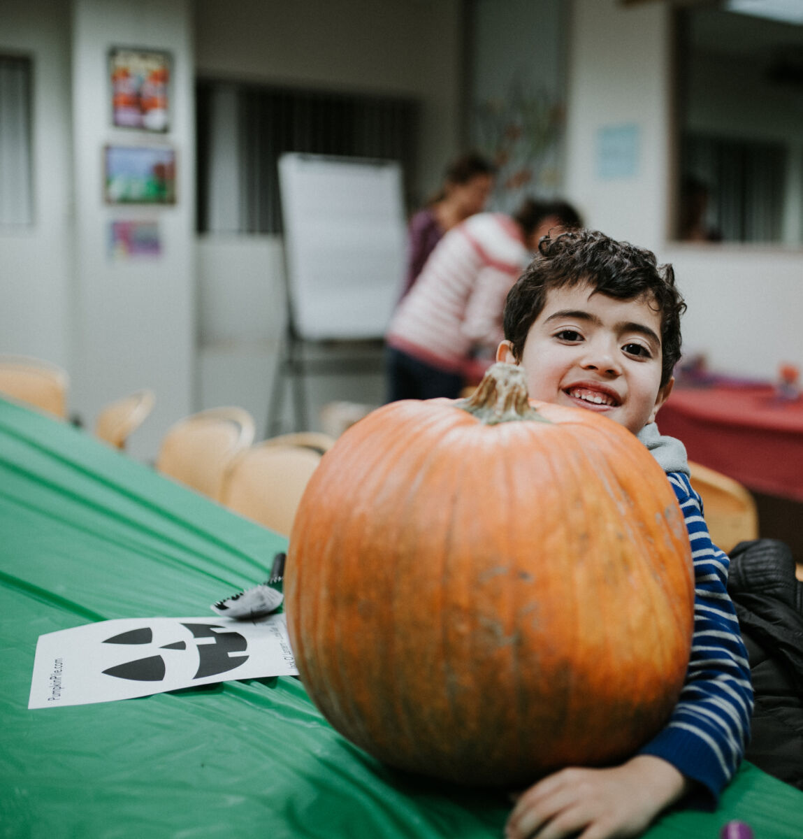 Young boy poses with large pumpkin