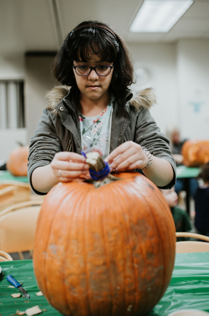 Young girl decorates her pumpkin